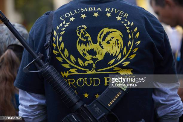 """Proud Boy member is armed with a gun labeled """"Zombie Killer"""" as members and supporters of Patriot Prayer gather in Esther Short Park for a memorial..."""