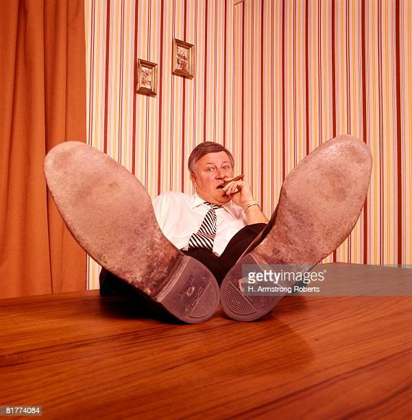 Proud businessman smoking cigar with feet propped on desk.