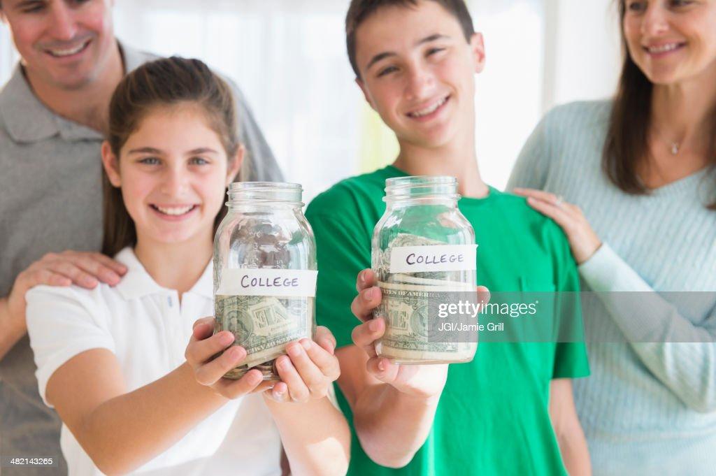Proud Caucasian parents watching children with college savings jars : Stock Photo