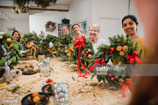 proud christmas wreath making workshop - country christmas stock pictures, royalty-free photos & images