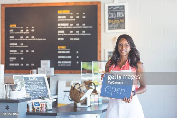 Proud coffee shop owner hold open sign on first day of business