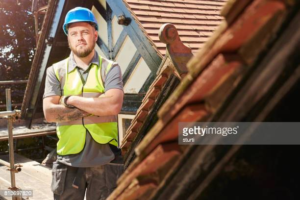proud construction worker on roof scaffold