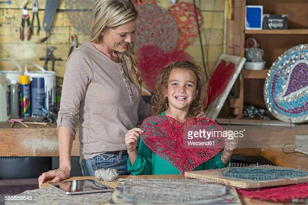 Proud daughter with mother presenting craftwork in home garage