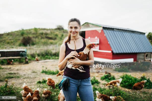 proud farmer smiling while holding chicken - simple living stock pictures, royalty-free photos & images