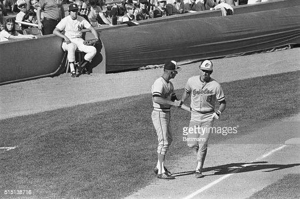 Proud Father and Son New York Baltimore Orioles 3rd base coach Cal Ripken Sr gives his son Cal Ripken Jr a hand shake and a pat on the back as Cal Jr...