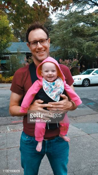 Proud father holding smiling newborn baby outdoors on sidewalk.