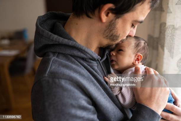 proud father kissing newborn son - newborn stock pictures, royalty-free photos & images