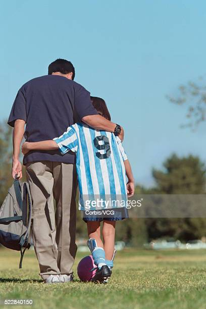 Proud father with arm around his daughter leaving the soccer field