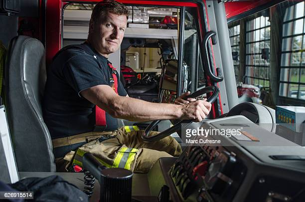 proud fireman with protection pants sitting behind steering in truck - fire station - fotografias e filmes do acervo