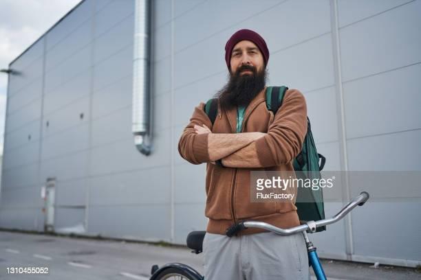彼の腕を組んだ誇り高い食糧配達宅配便は、長い都市の配達ルートの後に休んでいる間、彼の自転車に寄りかかっています - extra long ストックフォトと画像
