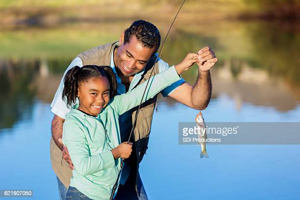 proud girl shows off fish while fishing with granddad - pequeno lago - fotografias e filmes do acervo
