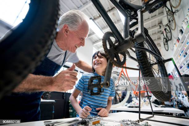 proud grandfather congratulating his grandson for a job well done on a bike at their family business - pedal stock pictures, royalty-free photos & images