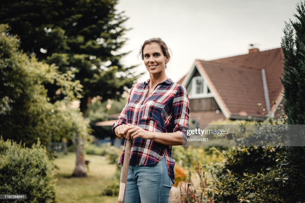 Proud home owner standing in her garden with a spade : Stock-Foto