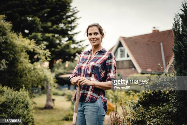 proud home owner standing in her garden with a spade - mid adult women stock pictures, royalty-free photos & images