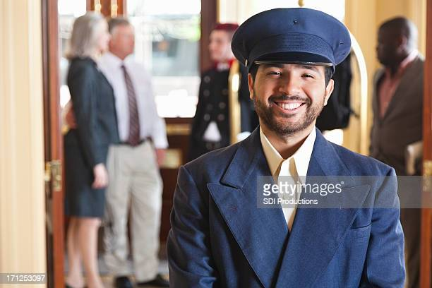 Proud hotel door man in front of guests and employees