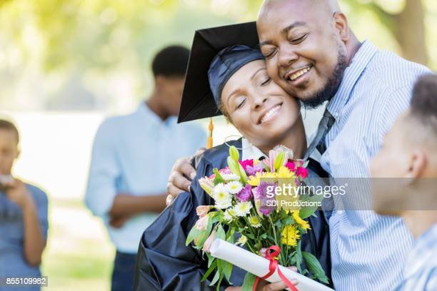 Proud husband hugs wife on her graduation day