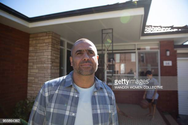 Proud Indigenous Aboriginal Australian man standing in front of his home