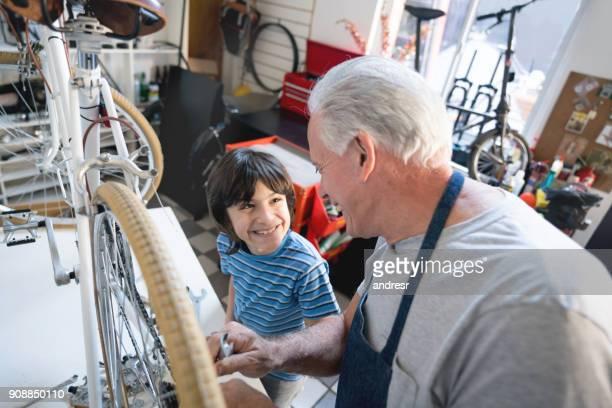 Fier petit garçon regardant son grand-père avec admiration, alors qu'il est la fixation de la bicyclette
