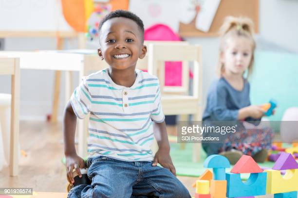 proud little boy smiles for camera beside his toy block tower - preschool age stock pictures, royalty-free photos & images