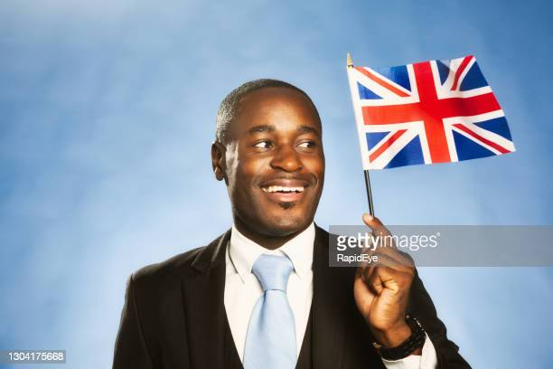 proud man holding the british flag, the union jack, smiles cheerfully at it - black history in the uk stock pictures, royalty-free photos & images