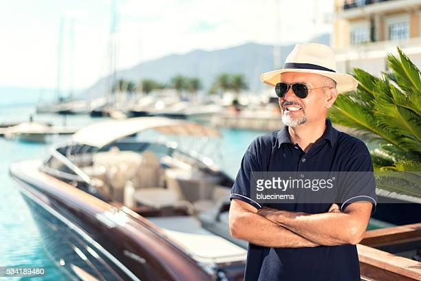Proud man in front of his yacht