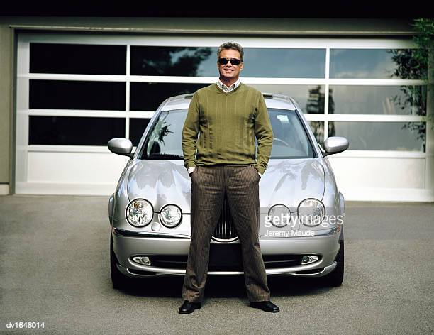 proud mature man standing on a driveway leaning on his car - appoggiarsi foto e immagini stock
