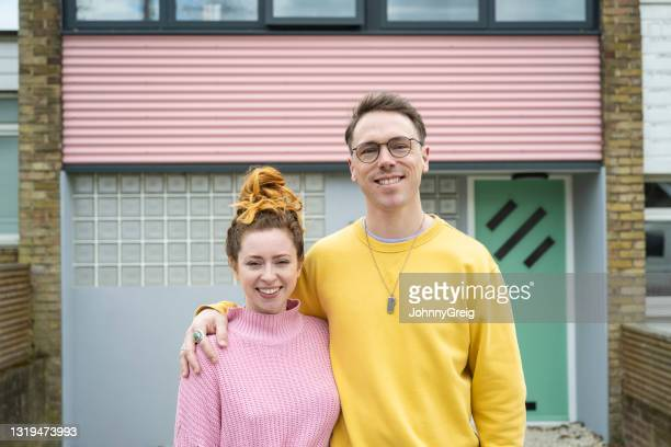 proud mid 30s home owners with arms around each other - standing stock pictures, royalty-free photos & images