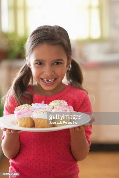 Proud mixed race girl holding cupcakes