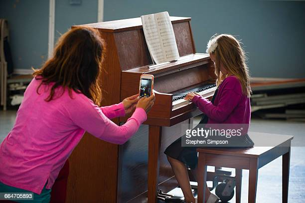 proud mom and her novice piano student