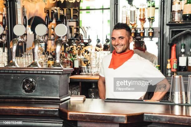 orgoglioso proprietario di un pub dietro il bancone - british culture foto e immagini stock