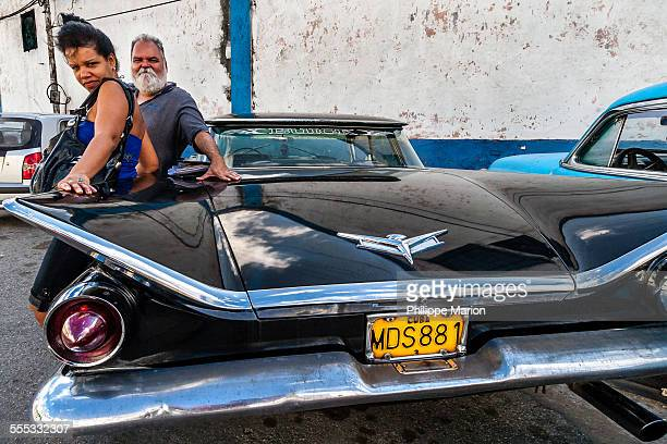 Proud owners of a 1959 Buick flat top await a friend at the Havana train station. Due to a decades old embargo Cubans rely on a fleet of 1950s era to...