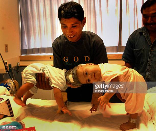 Wenceslao Quiej is all smiles as he lifts up his two conjoined twin daughters Maria de Jesus Quiej–Alvarez and Maria Teresa Quiej–Alvarez in their...