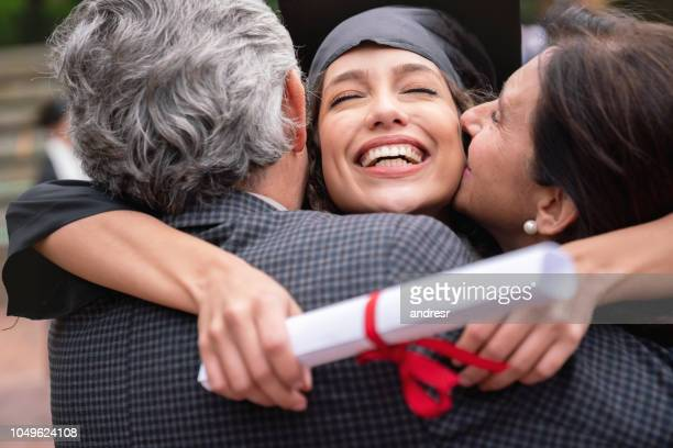 proud parents hugging their daughter and celebrating her graduation - high school graduation stock pictures, royalty-free photos & images