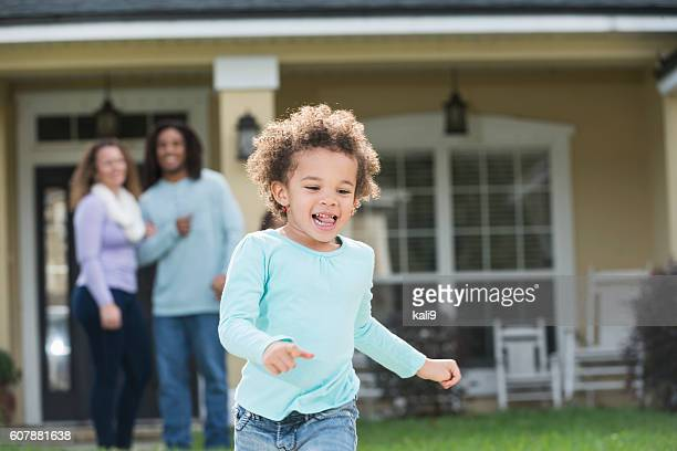 Proud parents watch young daughter run in front yard