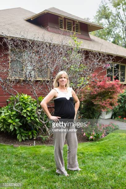 proud pregnant woman standing on front lawn smiling, with hands on her hips. - pasadena california stock pictures, royalty-free photos & images