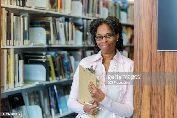 proud school librarian smiles for camera - school principal stock pictures, royalty-free photos & images