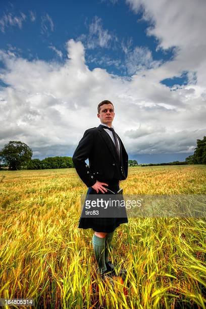 Proud scotsman in cornfield wearing kilt