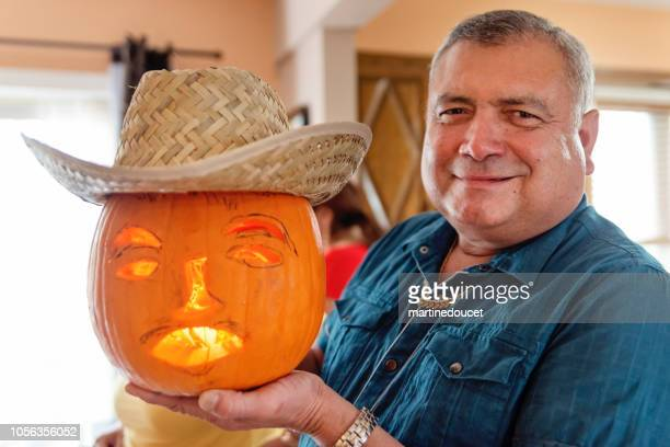 Proud senior Latin American man with his special hispanic pumpkin for Halloween