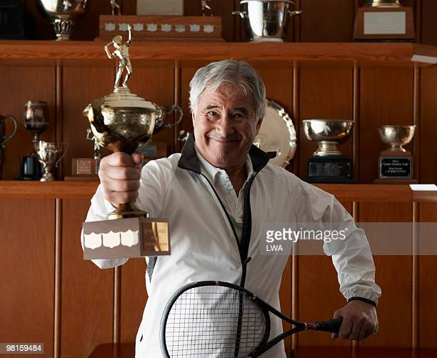 Proud Senior Man Holding Squash Trophy and Racquet