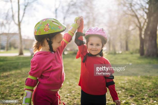 proud siblings learning how to ride rollerblades together - family with two children stock pictures, royalty-free photos & images