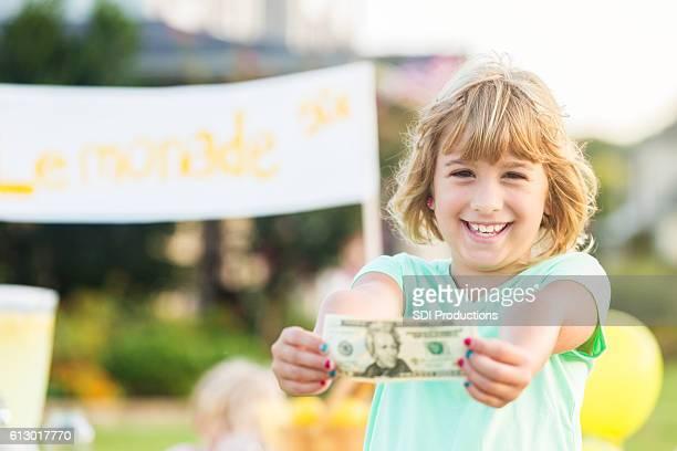 Proud small entrepreneur shows off profit