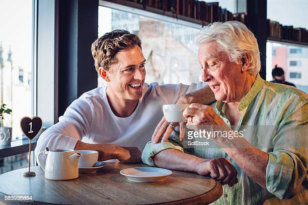 Proud son enjoying a coffee with his mature dad