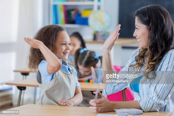 Proud teacher gives student a high five in math class