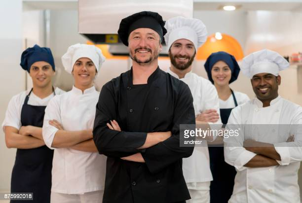proud team of chef, sous chefs and cooking assistants looking at camera smiling - chef stock pictures, royalty-free photos & images