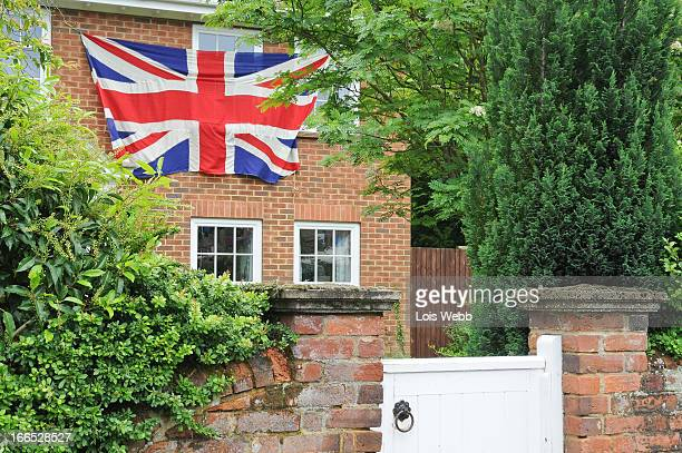 CONTENT] Proud to be British Traditional English red brick house with painted wooden gate and walled garden decorates the front with large Union Jack...
