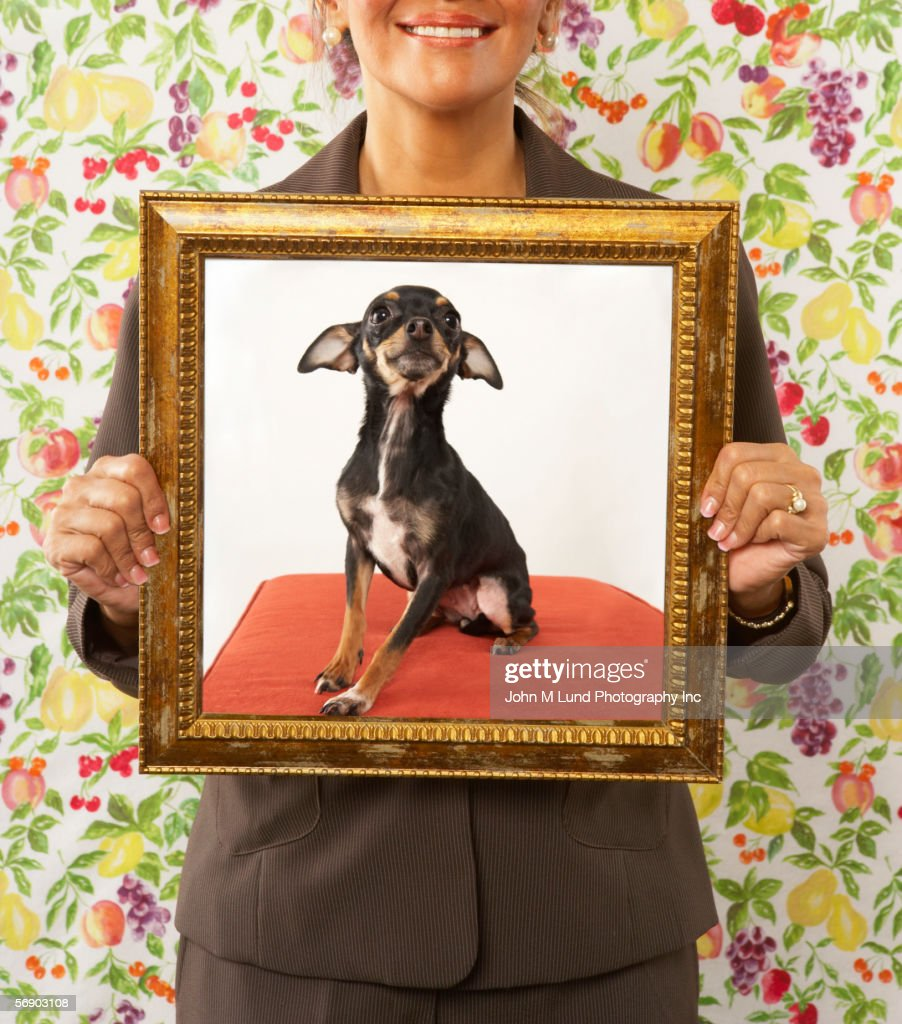 Proud woman holding framed picture of dog : Stockfoto