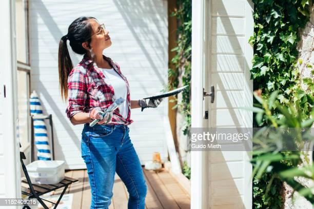 proud woman painting garden house. - landhaus stock-fotos und bilder