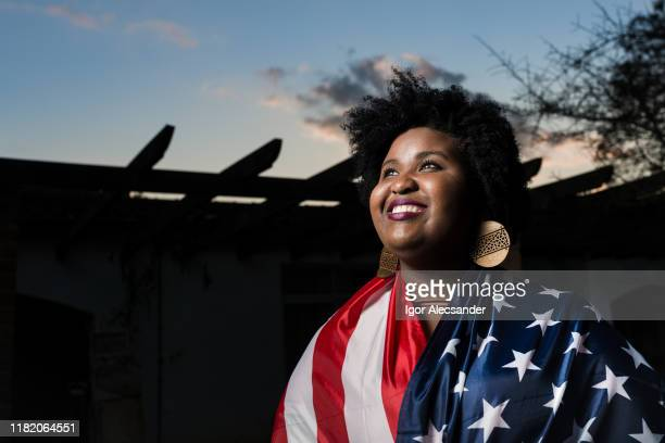 proud woman raising the flag of the united states of america - settler stock pictures, royalty-free photos & images