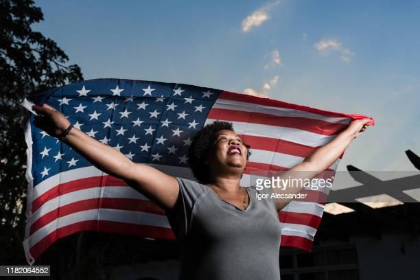 mulher orgulhosa que levanta a bandeira dos estados unidos da américa - emigration and immigration - fotografias e filmes do acervo