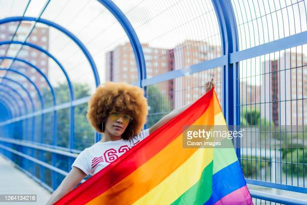 proud woman with her gay pride flag on a bridge - madrid stock pictures, royalty-free photos & images